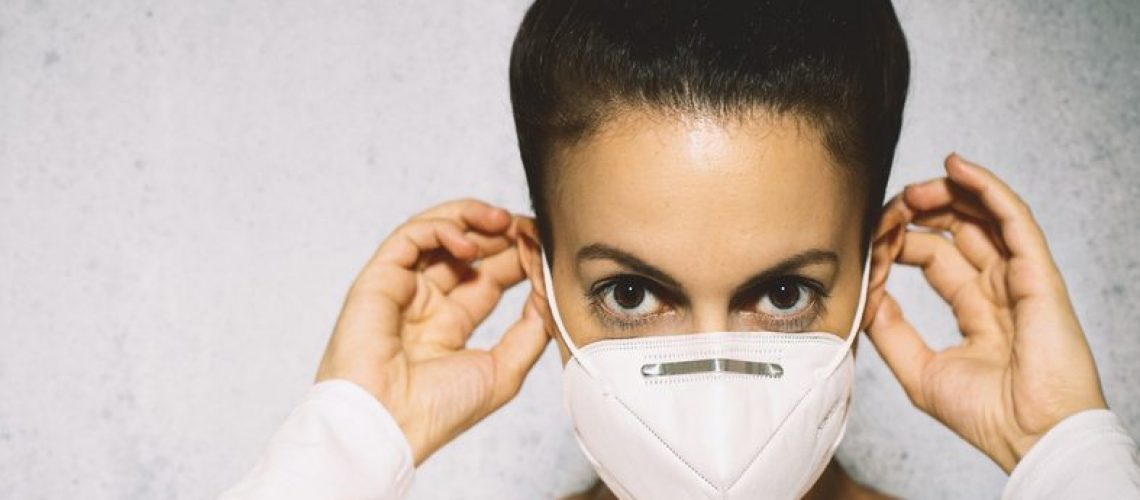 Portrait,Of,Young,Woman,Putting,Medical,Mask,On.